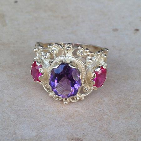 טבעת בסגנון ויקטוריאני מלכותית בשיבוץ אבן סגולה מרכזית ושתי אבנים ורודות בצדדים