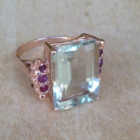 טבעת גדולה עם אבן מרובעת בצבע תכלת ואבני רובי קטנות בצדדים