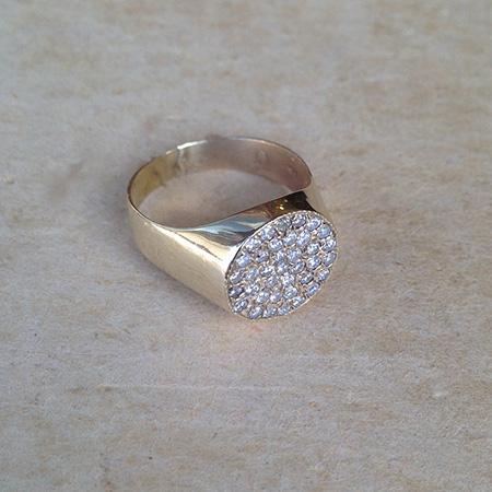 טבעת חותם יהלומים מונחת על משטח בהיר