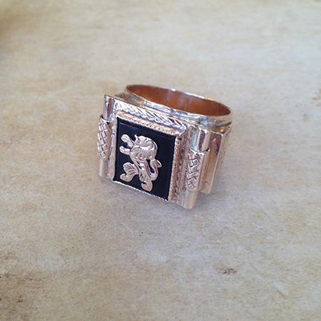 טבעת חותם גדולה לגבר עם סמל אריה מונחת על משטח בהיר