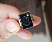 יד מחזיקה טבעת חותם מלבנית עם אבן שחורה וחריטת סמל קולג׳