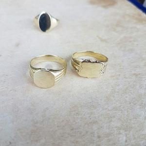 טבעת חותם מרובע וטבעת חותם מגן מזהב מונחות על רקע בצבע אבן