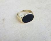 טבעת חותם אבן שחורה אובלית מונחת על משטח בהיר