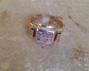 טבעת חותמת ישנה מקורית עם אות מרכזית ועיטורים בצדדים על משטח בהיר