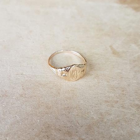 טבעת חותם קטנה עם ראשי תיבות על רקע בהיר