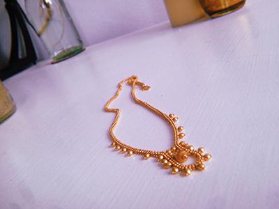 שרשרת זהב בסגנון הודי מונחת על שולחן לבן