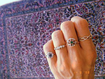 יד עונדת 4 טבעות יהלומים וינטג' עם רקע של שטיח צבעוני