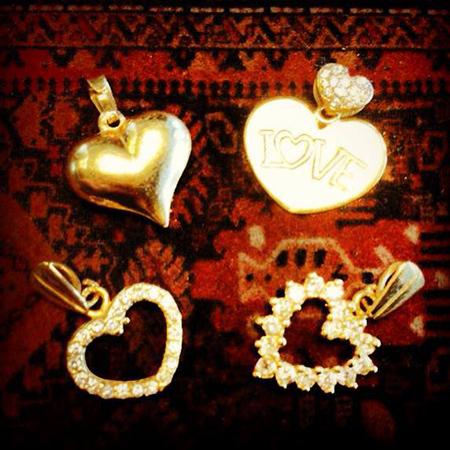 4 תליונים בצורת לב עשויים זהב על רקע אדום